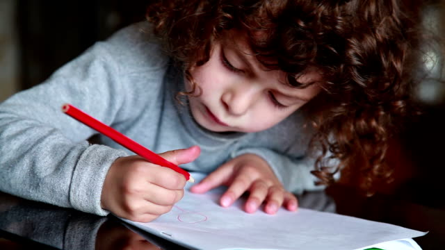 Little girl drawing a face with red pencil