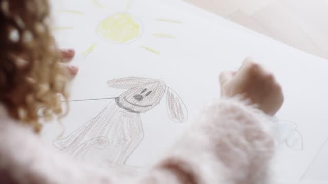 vídeos y material grabado en eventos de stock de niña dibujando y coloreando en la mesa de la cocina - pincel