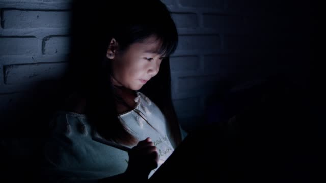 a little girl drawing something on digital tablet in her bedroom - adult imitation stock videos & royalty-free footage