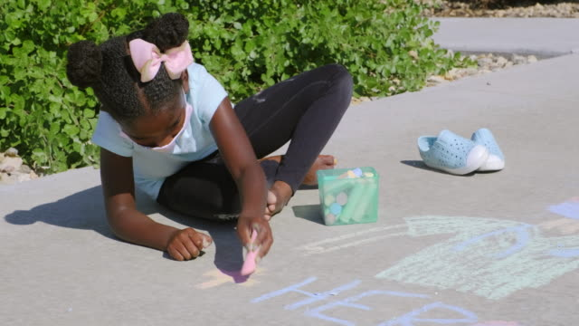 little girl drawing with sidewalk chalk to support healthcare workers - gessetto da lavagna video stock e b–roll
