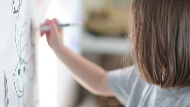小さな女の子は、ホワイトボード - 製図板点の映像素材/bロール