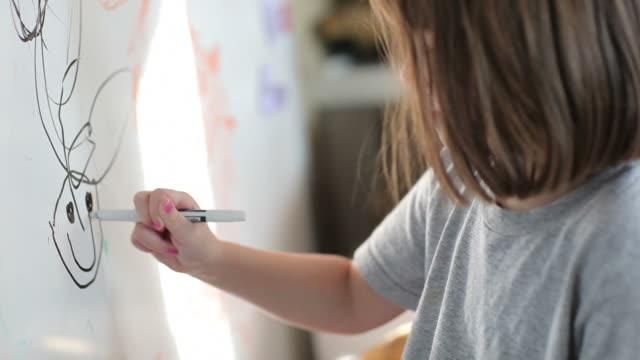 Little Girl Draws on White Board