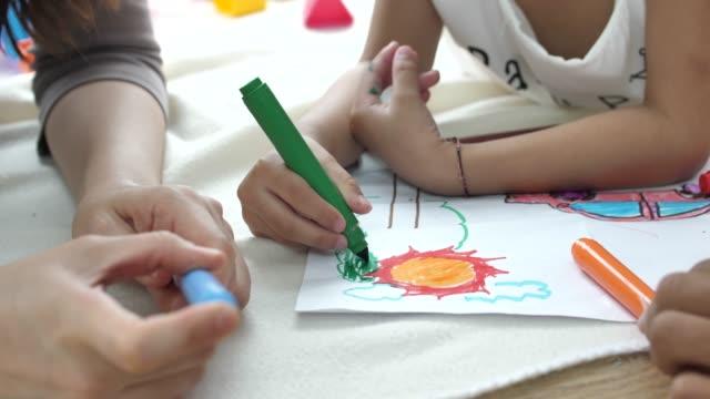 vidéos et rushes de petite fille dessine avec la mère - nurse