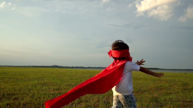 Little girl dressed as a superhero makes expressions and try to fly in the colorful nature