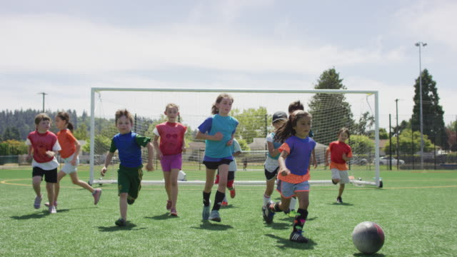 little girl dribbling soccer ball up a field - children only stock videos & royalty-free footage