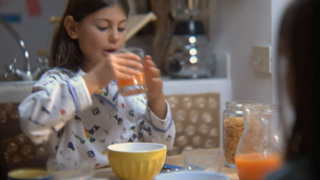 ms little girl drinking orange juice at breakfast table and smiling/ rome, italy - juice drink stock videos & royalty-free footage