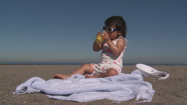 little girl drinking orange juice on beach - only baby girls stock videos & royalty-free footage
