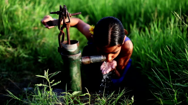 little girl drinking water near green field - povertà video stock e b–roll