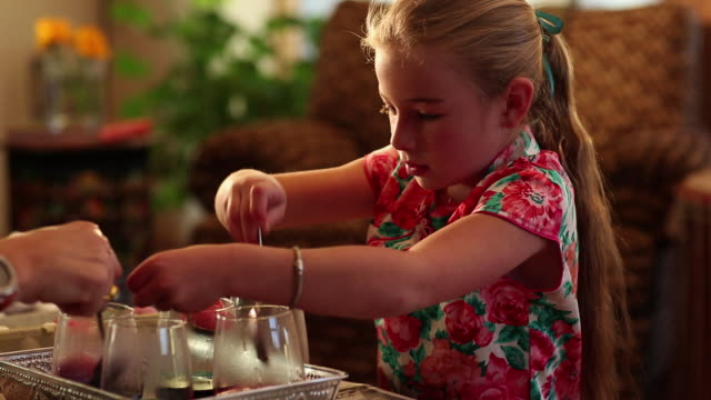 ms pan little girl dyeing easter eggs in color water  / lamy, new mexico, united states - lamy new mexico stock videos and b-roll footage