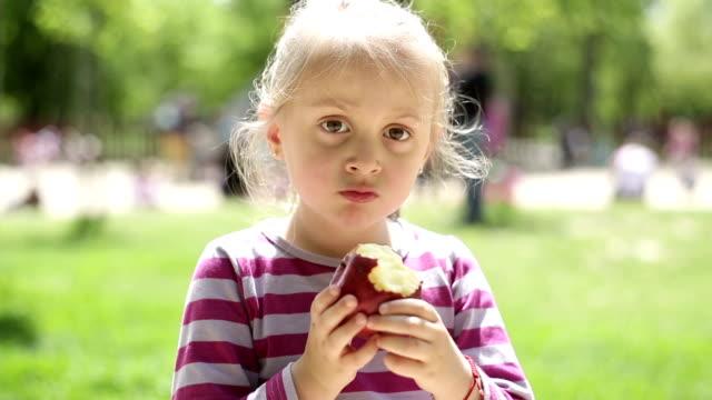 Kleine Mädchen Essen apple auf einem Spielplatz
