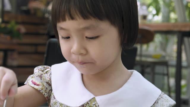 vidéos et rushes de petite fille manger la crème glacée au chocolat - enfance