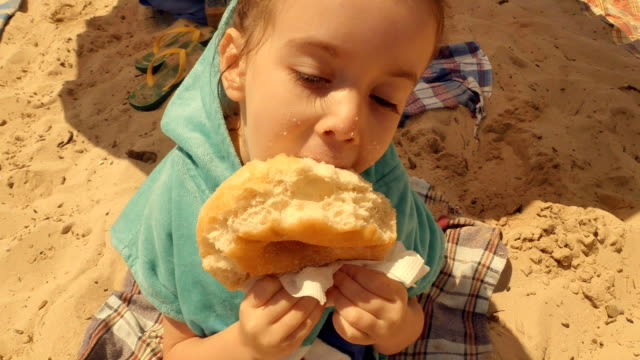 little girl eating donut at beach. - doughnut stock videos and b-roll footage