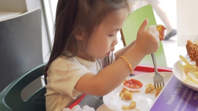vídeos de stock, filmes e b-roll de menina comendo batatas fritas e frango frito - cadeirinha cadeira