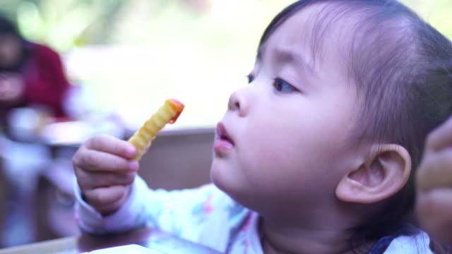 Little girl eating fried potatoes
