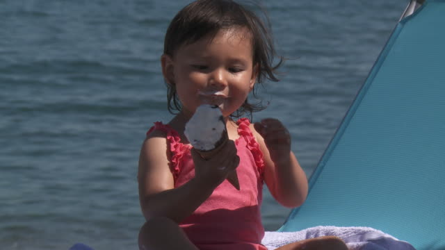 little girl eating ice cream cone on beach - one baby girl only stock videos & royalty-free footage