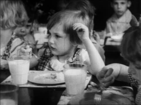 b/w 1934 little girl eating in nursery school / wpa project / newsreel - 1934 stock-videos und b-roll-filmmaterial