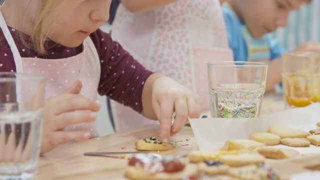 vídeos y material grabado en eventos de stock de niña comiendo mientras decoran galletas con sus amigas - al horno