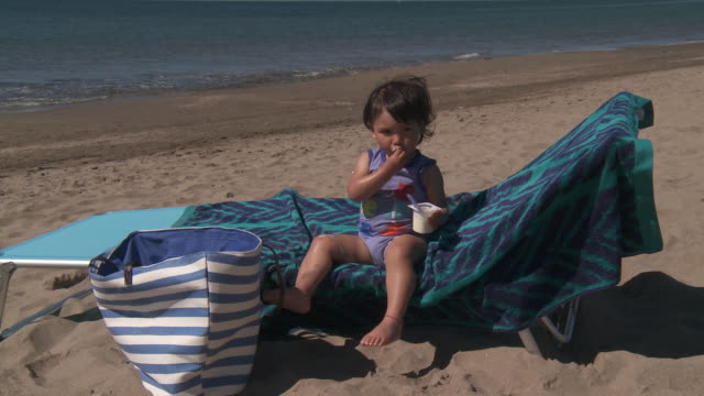 little girl eating yogurt on beach - one baby girl only stock videos & royalty-free footage