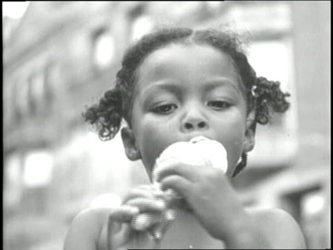 A little girl eats an ice cream cone