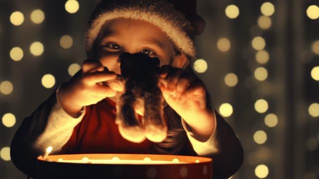 彼女はクリスマスのために得たテディベアを抱きしめる小さな女の子 - 知覚点の映像素材/bロール