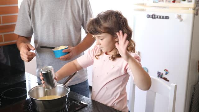 彼女の父が見ている間、コンデンスミルクを空にする小さな女の子は鍋の中でできます - dia点の映像素材/bロール