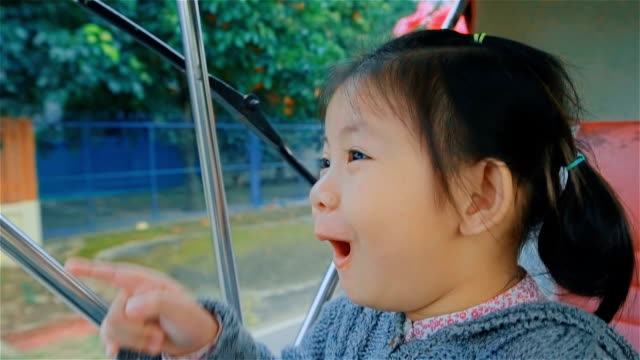 Little girl enjoying a horse drawn carriage ride in temple Phrathat Lampang Luang in Lampang, Thailand