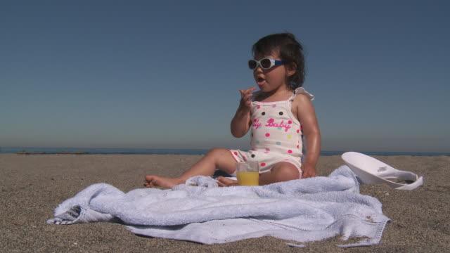 little girl enjoying an orange juice at the beach. - sun visor stock videos & royalty-free footage