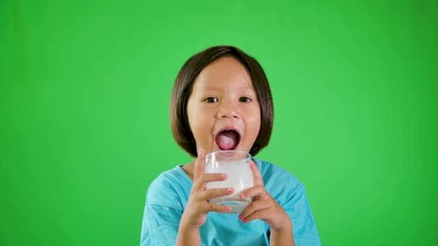 little girl enjoying her cup of milk on green background. - refreshment stock videos & royalty-free footage
