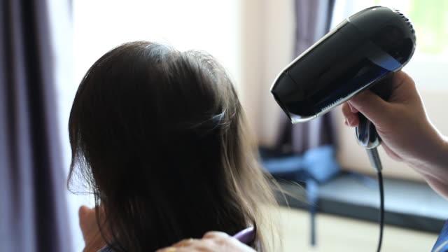 vídeos de stock, filmes e b-roll de menina, apreciando o cabelo dela é secado por um cabeleireiro - secar