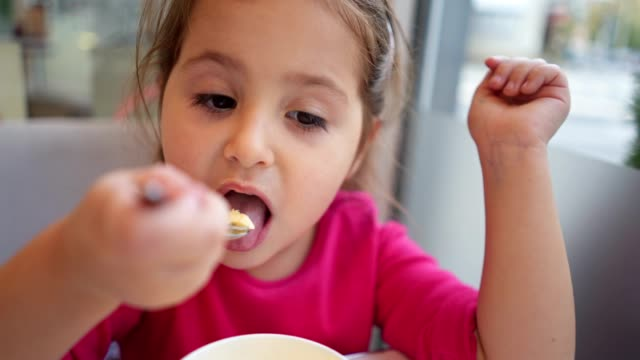 little girl enjoying ice cream while looking at the phone - human tongue stock videos & royalty-free footage