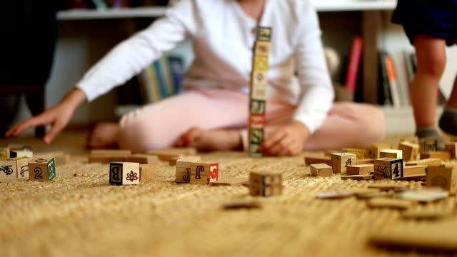 little girl enjoys building with toy blocks on floor - toy block stock videos and b-roll footage