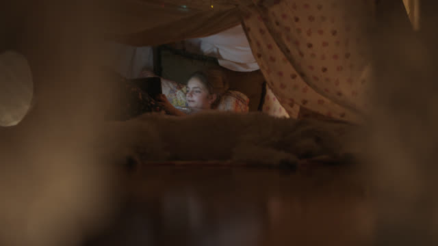 little girl enjoys her tablet while inside her blanket fort. - fortress stock videos & royalty-free footage
