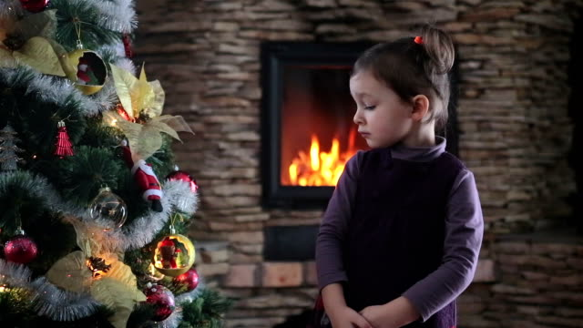 little girl examines the christmas tree with great curiosity. - admiration stock videos and b-roll footage