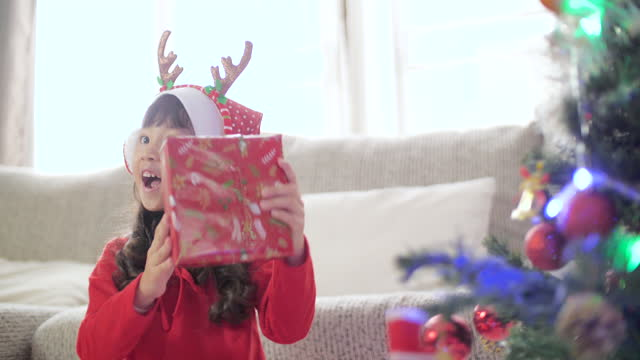 little girl excited and shaking presents before opening on christmas day - unwrapping stock videos & royalty-free footage