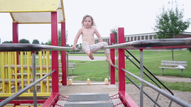 ms tu little girl experiments on monkey bars at playground / toronto, ontario, canada  - shirtless stock videos and b-roll footage
