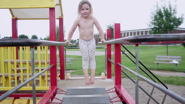 ms little girl experiments on monkey bars at playground / toronto, ontario, canada  - nackter oberkörper stock-videos und b-roll-filmmaterial