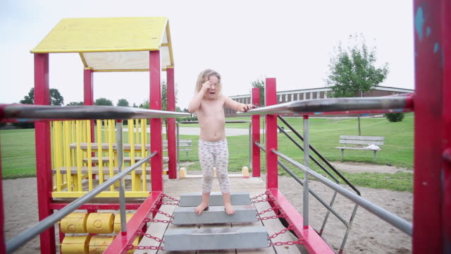 ms little girl experiments on monkey bars at playground / toronto, ontario, canada  - kelly mason videos stock videos & royalty-free footage