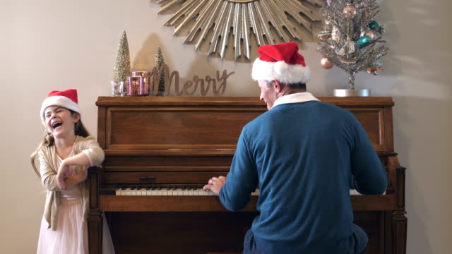 little girl, father at piano, christmas and santa hats - cantare video stock e b–roll