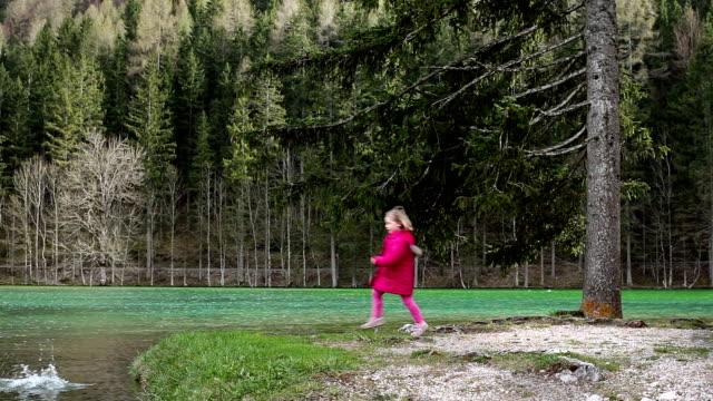 vídeos de stock e filmes b-roll de hd: rapariga alimentação patos - pequeno lago