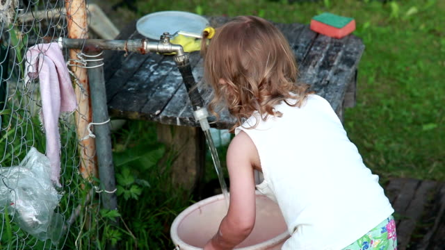 vídeos de stock e filmes b-roll de little girl filling a bucket with water from the garden tap - balde