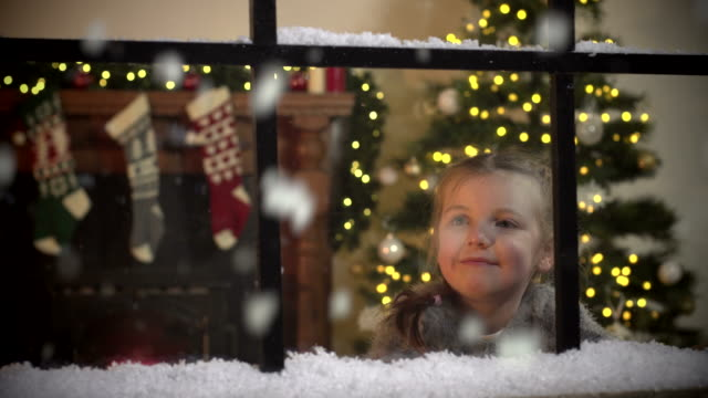 little girl gazing at snow falling through window at christmas - stockings stock videos & royalty-free footage