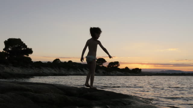 Little Girl Gesturing At a Beach in Sunset
