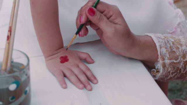 Little girl get painted hand for a carnival