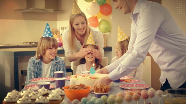 Kleines Mädchen bekommt einen Kuchen für den 6. Geburtstag