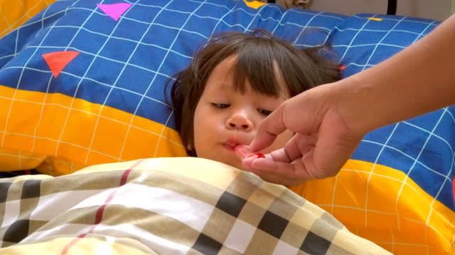 Petite fille à obtenir un contrôle de température avec un thermomètre numérique.