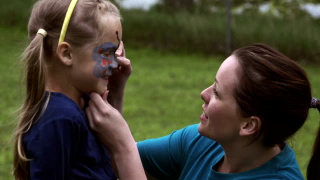 Little girl getting her face painted at camp