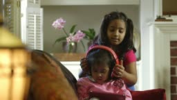 Little girl gives the headphones to her little sister