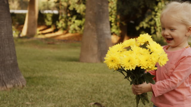 Little girl giving yellow flowers to mother