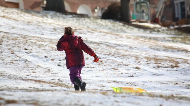 little girl glancing back at camera as she pulls a sled up a snowy hill. - kelly mason videos 個影片檔及 b 捲影像