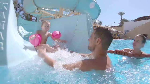 little girl goes down the water slide into the pool. - tourist resort stock videos & royalty-free footage